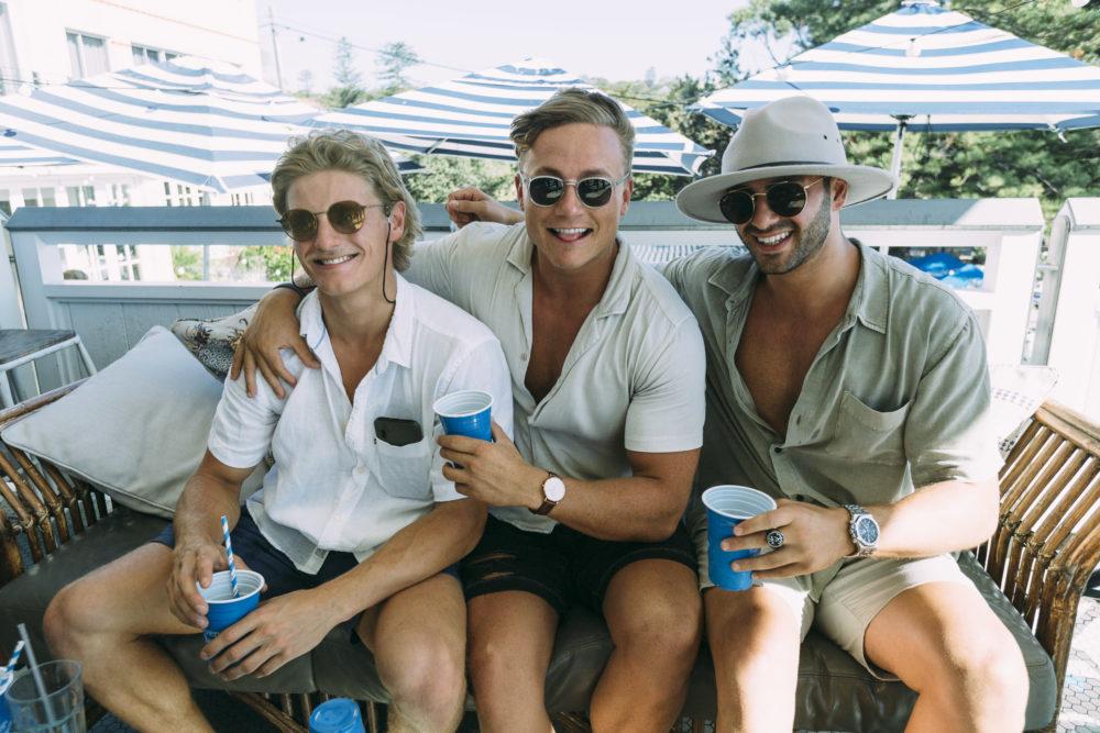 Three men having drinks together on the balcony