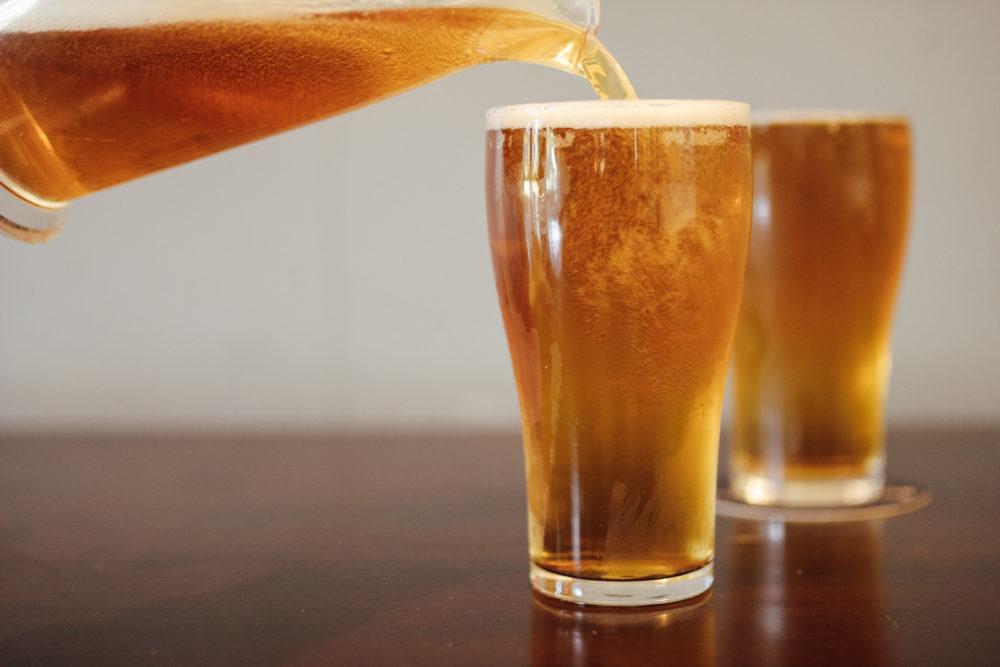 Schooner of beer being poured from a beer jug