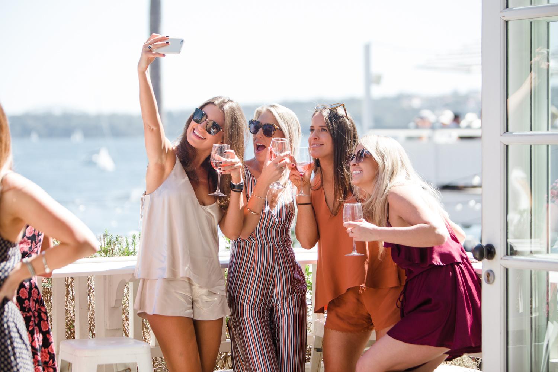 Four girls taking a selfie on a balcony.