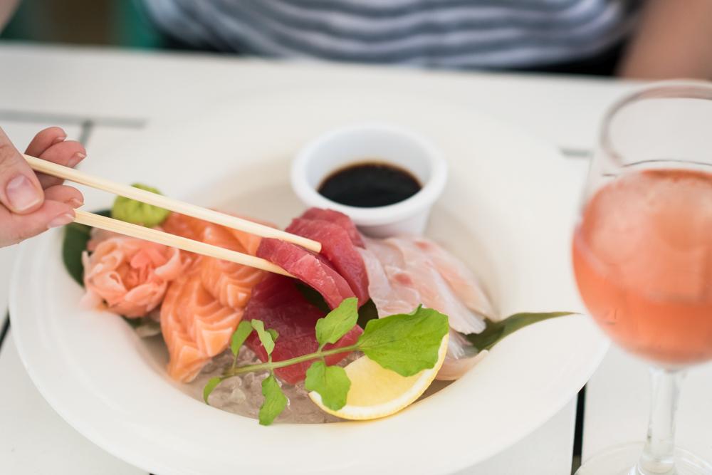 A customer enjoying Colourful and Fresh Sashimi with chopsticks